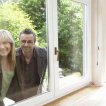 Ein Paar schaut durch ein Fenster in eine freie Immobilie.